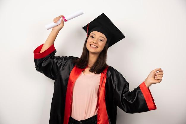白い背景の上に立っているガウンの大学卒業生の女性。