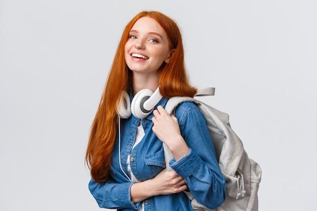 대학 생활, 현대적인 생활 방식 및 교육 개념. 폭시 긴 머리를 가진 쾌활한 잘 생긴 빨간 머리 여학생, 목에 헤드폰을 끼고, 배낭, 웃는 카메라.