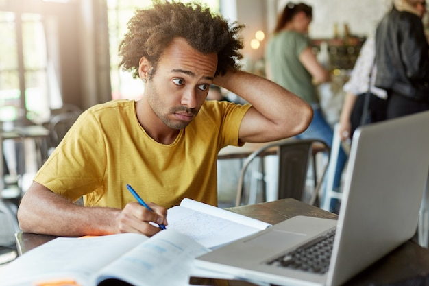 College male student with african hairstyle sitting at wooden desk in cafeteria writing down something from laptop computer in his exercise book