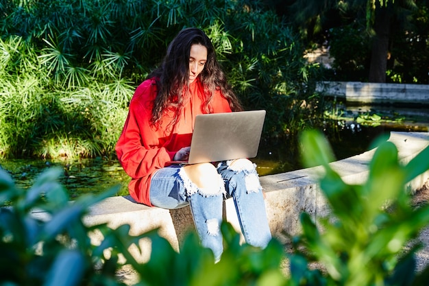 College student girl sitting in the park working with laptop