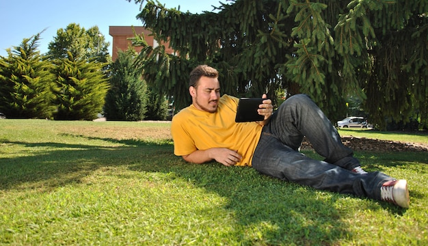 College student lying on the grass in the sun with a tablet
