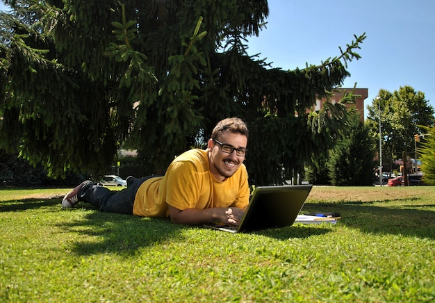 College student lying on the grass in the sun