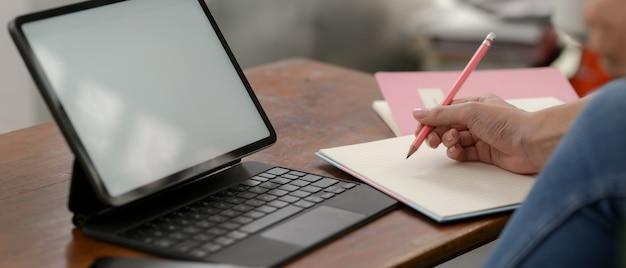 大学生のモックアップタブレットでのオンライン学習と空白のノートブックでメモを取る