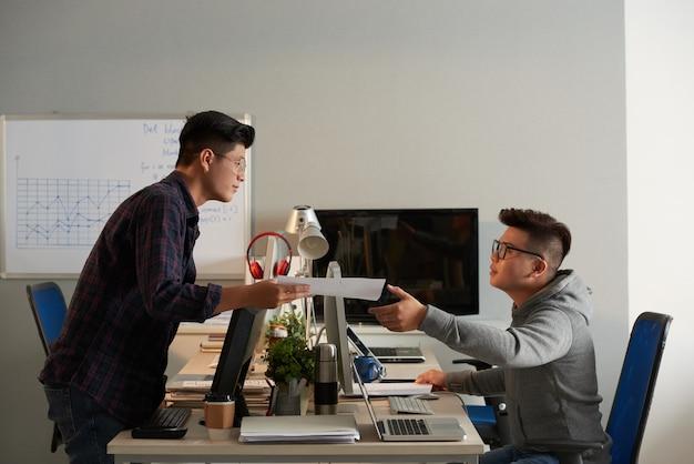 彼らがコンピューティングで一緒にプロジェクトに取り組んでいるときに彼の友人にドキュメントを渡す大学生...