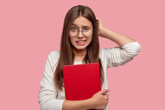 Студентка в недоумении чешет затылок, стискивает белые зубы, запоминает информацию перед тем, как ответить на выпускном экзамене, держит красную тетрадь, чувствует недовольство, проблемы с учебой.