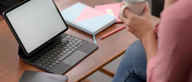 大学生がリビングルームでモックアップタブレットを使ってオンラインで勉強しながらコーヒーで休憩