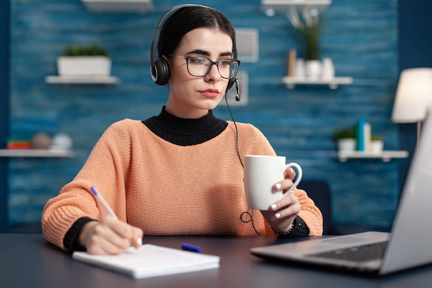 大学のウェブサイトでオンラインコースの情報を検索しながら、紙にメモをとっている大学生。リビングルームの机に座ってラップトップコンピューターを使用して若い女性