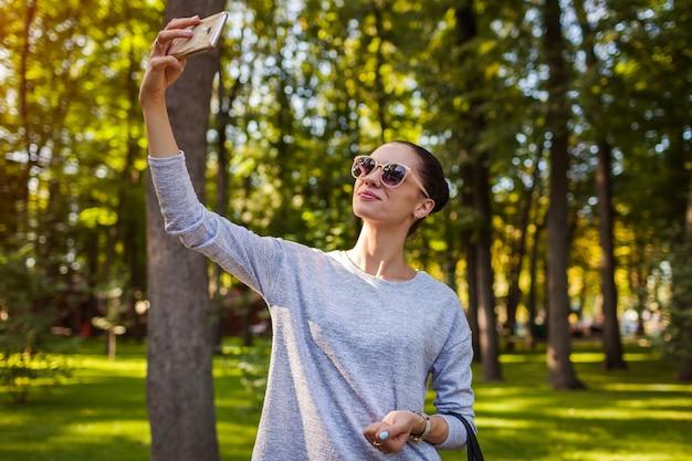公園で携帯電話で自撮りをしている大学生