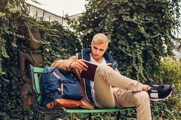 College student with backpack reading book chilling by modern hotel on rainy autumn day