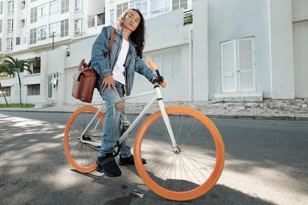 信号を待っている自転車に座っている大きな革のバッグを持つ大学生