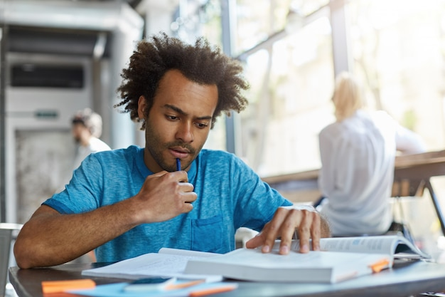 턱에 펜을 들고 책에서 중요한 것을 읽는 동안 곱슬 머리와 강모가 집중된 대학생. 하루 종일 열심히 공부하는 열심히 일하는 남자