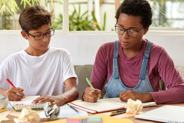 Gli studenti universitari si sono concentrati sulla scrittura, siedono al desktop, prendono appunti sul taccuino