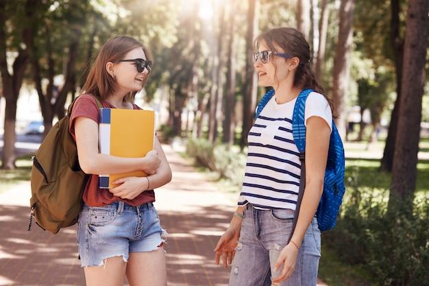 Студенты колледжа случайно встречаются в парке, носят сумки и книги, приятно беседуют, обсуждают последние новости в университете, готовятся к летним экзаменам. люди, учеба и дружба