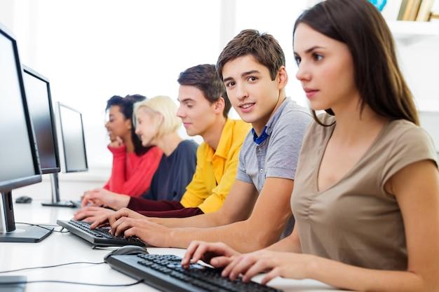 Студенты колледжа сидят в классе и используют портативные компьютеры во время занятий (неглубокая глубина резкости)