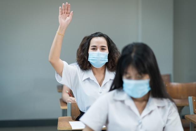 大学生は教室でフェイスマスクの勉強をし、コロナウイルスのパンデミックの間に先生に尋ねるために手を上げます。教室で勉強する大学生の選択的な焦点の肖像画。
