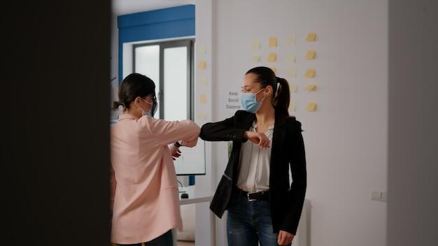 コロナウイルス検疫中にスタートアップ企業のオフィスで働いている間、肘でお互いに挨拶するフェイスマスクを持った同僚。ウイルス感染を防ぐために社会的距離を尊重するチーム