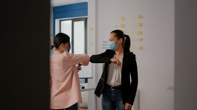 Collegues with face masks greeting each other with elbow while working in startup company office during coronavirus quarantine. team respecting social distancing to prevent infection with virus