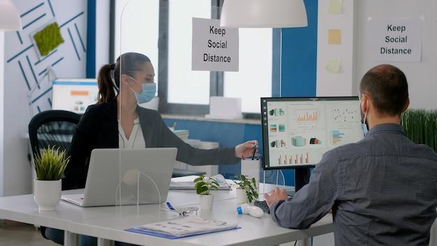 보호용 안면 마스크를 쓴 동료들은 적외선 온도계를 사용하여 온도를 확인한 후 사무실에서 일하기 시작합니다. 코로나19 감염 예방을 위한 사회적 거리두기 팀