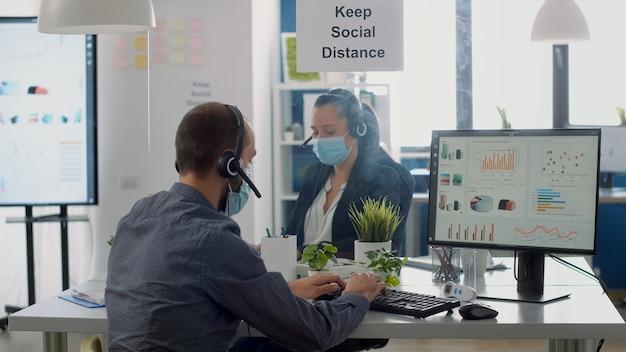 コロナウイルスのパンデミックの間、管理プロジェクトの営業所で働いている保護医療用フェイスマスクとヘッドフォンと同僚。ウイルス病を予防するために社会的距離を保つ同僚