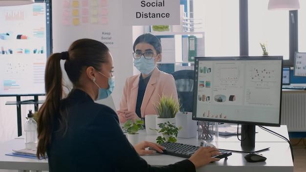 職場のオフィスでのビジネスプロジェクトについて話している机に座っている保護医療フェイスマスクと同僚。世界的大流行の際にウイルス病を回避するために社会的距離を保つ同僚