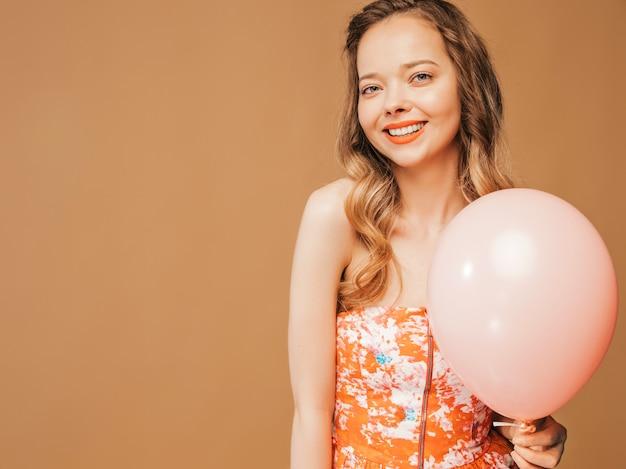 トレンディな夏colofrulドレスでポーズをとって興奮している若い女の子の肖像画。ピンクのバルーンポーズで笑顔の女性。パーティーの準備ができたモデル