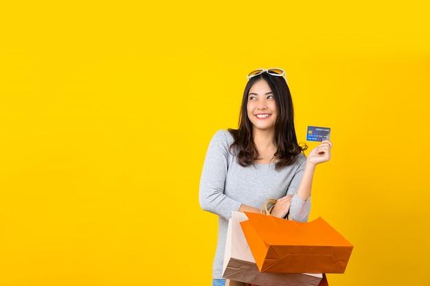 Счастливая азиатская усмехаясь женщина используя кредитную карточку и нося сумку покупок coloful для представлять покупки онлайн на изолированной желтой стене, космосе экземпляра и студии, продаже сезона черной пятницы