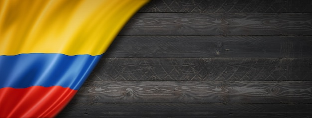 Colombia flag on black wood wall. horizontal panoramic banner.