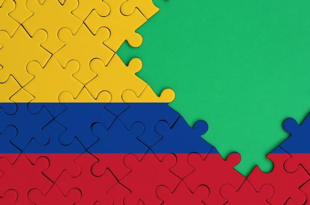 콜롬비아 국기는 오른쪽에 무료 녹색 복사 공간이있는 완성 된 직소 퍼즐에 그려져 있습니다.