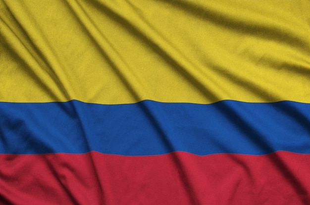 Colombia flag is depicted on a sports cloth fabric with many folds.