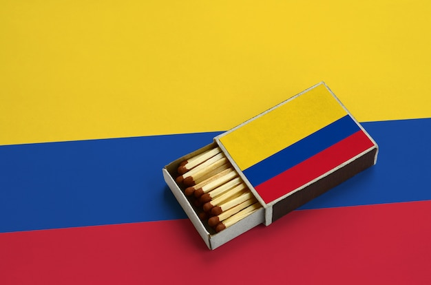 Colombia flag  is shown in an open matchbox, which is filled with matches and lies on a large flag