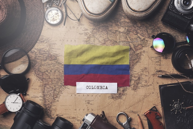 Colombia flag between traveler's accessories on old vintage map. overhead shot