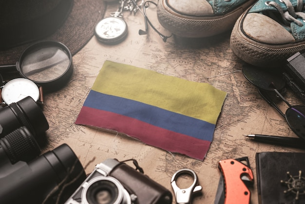 Colombia flag between traveler's accessories on old vintage map. tourist destination concept.