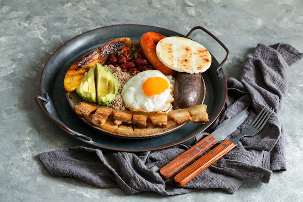 Colombian food. bandeja paisa, typical dish at the antioquia region of colombia - chicharron (fried pork belly), black pudding, sausage, arepa, beans, fried plantain