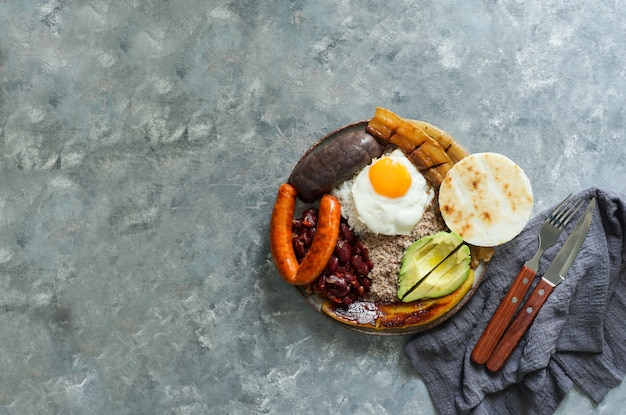 Colombian food. bandeja paisa, typical dish at the antioquia region of colombia - fried pork belly , black pudding, sausage, arepa, beans, fried plantain, avocado egg, and rice.