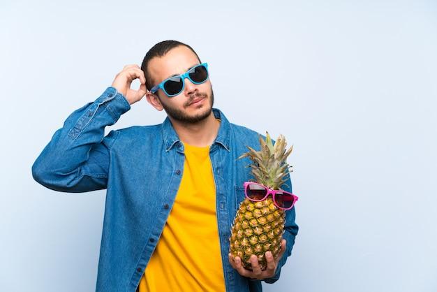 Колумбийский мужчина держит ананас с очками, думая, идея