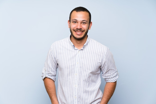 Colombian man over isolated blue wall laughing