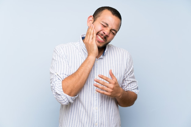 Colombian man over isolated blue wall with toothache