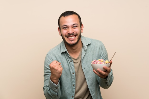 Colombian man with bowl of cereals celebrating a victory