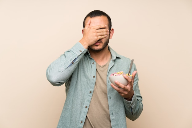 Colombian man with bowl of cereals covering eyes by hands