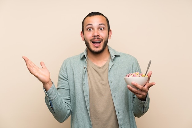 Colombian man with bowl of cereals with surprise and shocked facial expression