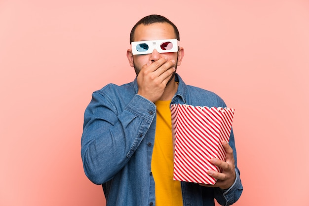 Colombian man with popcorns covering mouth with hands