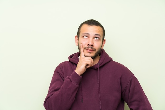 Colombian man with sweatshirt over green wall thinking an idea