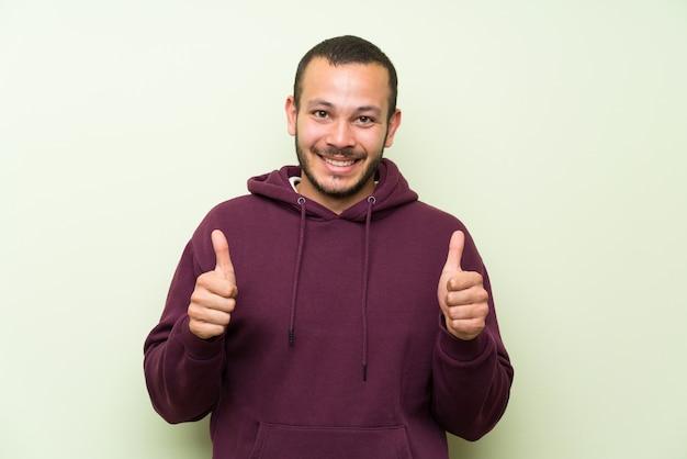 Колумбийский мужчина с толстовкой над зеленой стеной, давая пальцы вверх жест