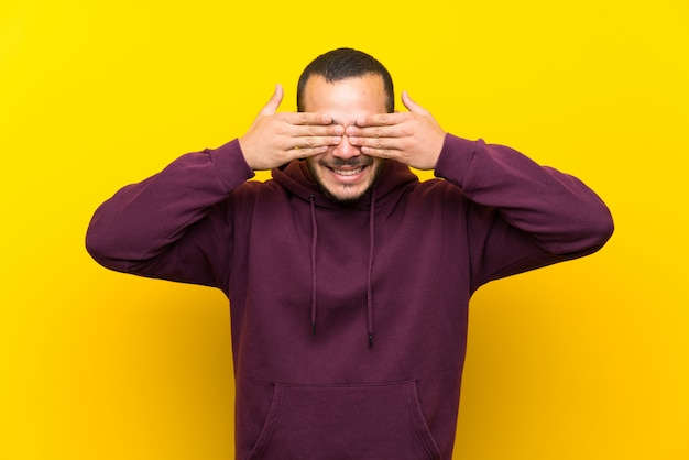 Colombian man with sweatshirt over yellow wall covering eyes by hands