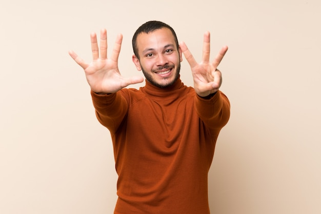 Colombian man with turtleneck sweater counting eight with fingers