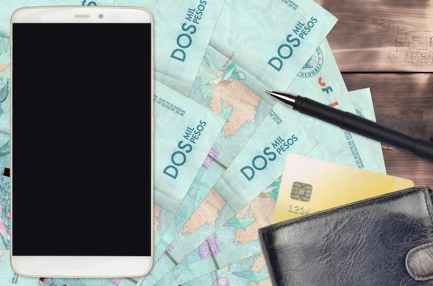 コロンビアペソ紙幣と財布とクレジットカード付きのスマートフォン