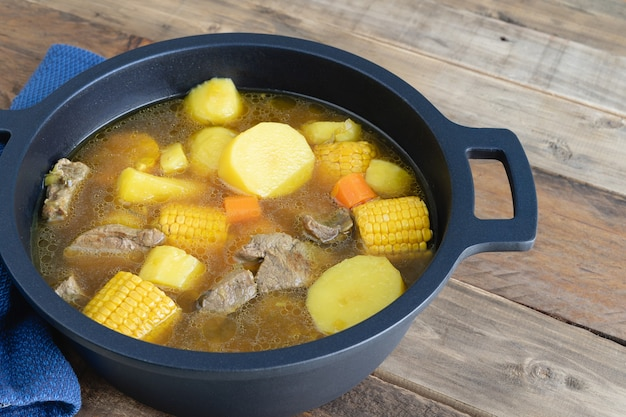 Colombian sancocho freshly made in a pot on a wooden bottom. copy space.