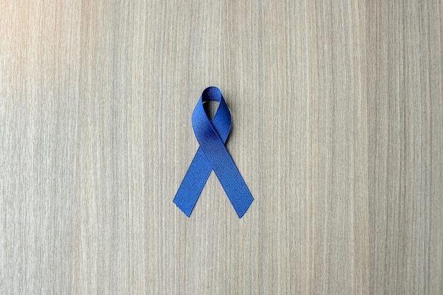 Colon cancer awareness, dark blue ribbon on wooden background