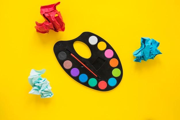 Matrice di colori con pennello e carta stropicciata
