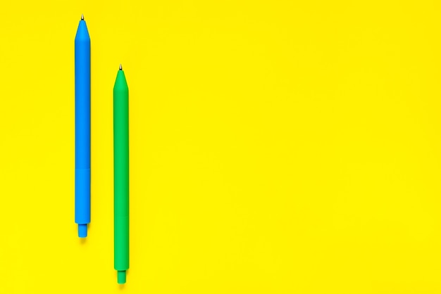 Color blue green pens on yellow background.